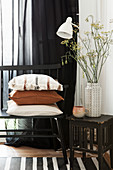 Black bench with cushions and vase of fennel flowers on wooden stool