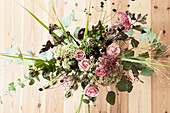 Autumn bouquet with roses, eucalyptus, love-in-a-mist seed heads, great burnet, sedum, pink pepper and chrysanthemums