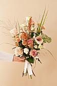 Hand hält Strauß mit Rosen, Kalla, Chrysanthemen, Nelken, Amaranth, Fetthenne, Strandflieder und Gräsern