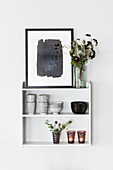 Bowls, beakers, flowers, tealight holders and picture on wall-mounted shelves