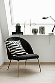 Black easy chair with black-and-white scatter cushion next to window