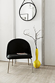 Branches in yellow vase next to black chair below mirror on wall