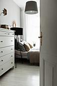 Blick neben Kommode auf Bett und Stehlampe im Schlafzimmer