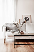 Scatter cushion and fur rug on white couch behind coffee table
