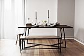 Gedeckter Tisch mit Kerzen, Sitzbank und Hocker