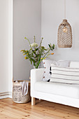 Pendant lamp above white couch and spring bouquet in corner