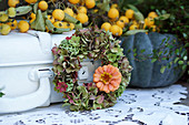 Wreath of hydrangeas with one zinnia flower, branch of crabapples and pumpkin
