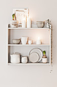 Crockery and white candles on wall-mounted shelves