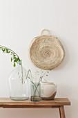 Grasses and leaves in demijohn, glass vase and ceramic vase on wooden bench