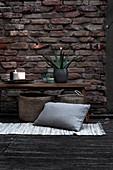 Holzbank mit Pflanze und Kerzen darunter Korbtaschen, Teppichvorleger und Kissen auf Terrasse