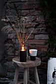 Trockenblumen, Kerze und Becher auf Holzhocker