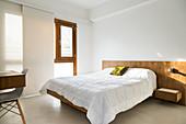 Doppelbett mit Kopfende aus Holz im Schlafzimmer mit Betonboden