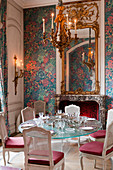 Hot pastel wallpaper in dining room with french chimney piece, glass table and painted Louis XV chaises