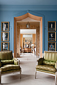 A pair of Louis XVI armchairs in front of doorway framed by regency pictures