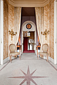 Pair of Louis XVI style dining chairs and gilt wall sconces in hallway with star-cut marble flooring