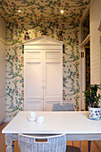 Floral chinoiserie wallpaper in kitchen with white painted furniture and exposed brick work. On top of the recessed pedimental cupboard sit 3 19th century chinese Famille Rose figures