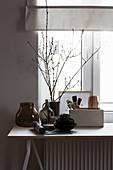 Geschirr, Glasgefäße und Zweige auf Tisch vor Fenster
