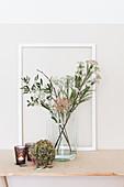 Hydrangea flower next to flowering branches in glass vase