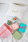 Multi-colored gift boxes on white bed and 'JOY' spelled with cards