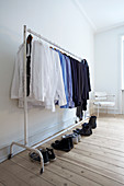 Shoes lined up below shirts hung on clothes rail