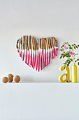 Love heart made from pink-painted twigs, yellow decorative letters and vase