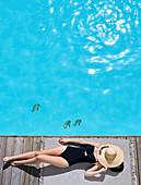 Frau im Badeanzug am Poolrand liegend, Gesicht mit Strohhut verdeckt