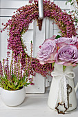 Autumn arrangement with heather wreath, vase of roses and potted ling