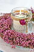 Windlicht im Heidekranz, dekoriert mit Rosenblüte und Schleierkraut