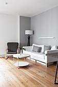 Weißes Sofa, Sessel und runder Couchtisch im grau-weißem Wohnzimmer