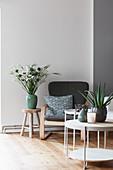 Runder Couchtisch, Sessel und Hocker mit Blumenvase
