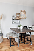 Dining table with dark wooden top, black chairs, fur blanket on bench and pendant lamps