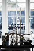 Silver candlesticks with white candles and antlers on black table