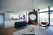 Küche und Sitzbereich in offenem Wohnraum mit Glasfront