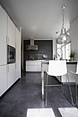 White cupboard and counter with bar stools in kitchen with concrete floor