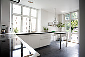 White cupboards in kitchen with concrete floor