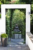 Statue of Buddha and box balls in Zen garden