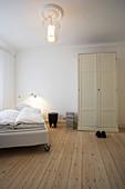 Bed on castors in room with pale board floor