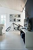 Fernsehregal und Fahrrad im Wohnzimmer mit weißem Dielenboden und teilweise schwarzer Wand