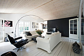 Loose-covered sofa and armchair next to arc lamp in black-and-white living room