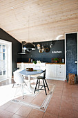 Breakfast table with various chairs in white fitted kitchen with black wall