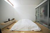 Double bed with white bedspread and wardrobe with frosted glass doors in bedroom