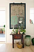 Plants on antique wooden table below Oriental artwork on wall