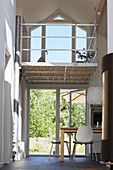 Esstisch mit weißen Stühlen im Erdgeschoss, in transparentem Haus