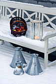 basket of apples and lantern on white wooden bench in snow