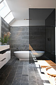 Free-standing bathtub in bathroom with slate tiles and skylight