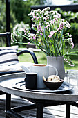 Coffee pot, biscuits and vase of flowers on terrace table