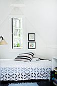 Bed with crocheted blanket in room with pitched ceiling
