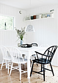 Black and white chairs in dining area of room with white, wood-clad walls