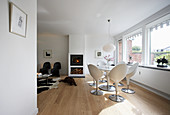 Classic chairs around dining table next to window in open-plan interior