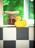 Gelbe Badeente auf schwarz-weißen Fliesen